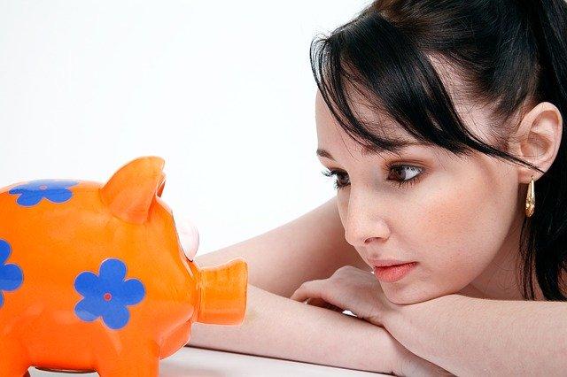 Mladá žena se dívá na prasátko ke spoření